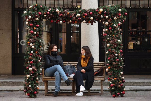 26 November 2020, England, London: Two women sit on a bench festively decorated with the Christmas Baubles, in Covent Garden. Photo: Yui Mok/PA Wire/dpa