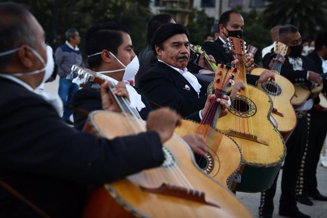 """22 November 2020, Mexico, Mexico City: Members of a Mariachi band perform in front of the monument to the Revolution as part of an activity called """"#SalvemosAlMarichi"""" which demands financial support from the government to musicians that have suffered eco"""