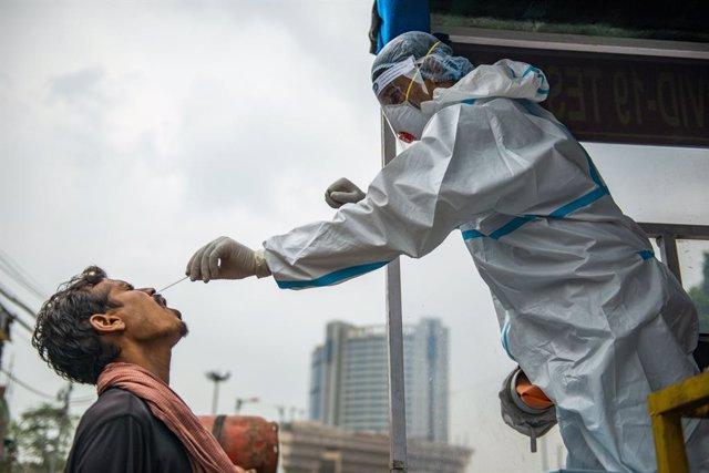 Un trabajador sanitario realiza un test a un ciudadano indio.