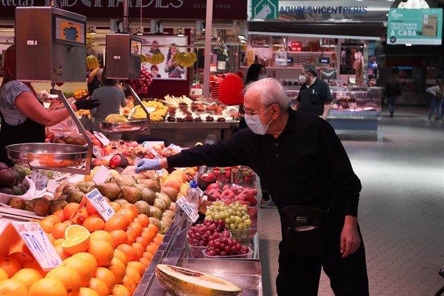 Un cliente señala la pieza de fruta que quiere en una frutería de un mercado central