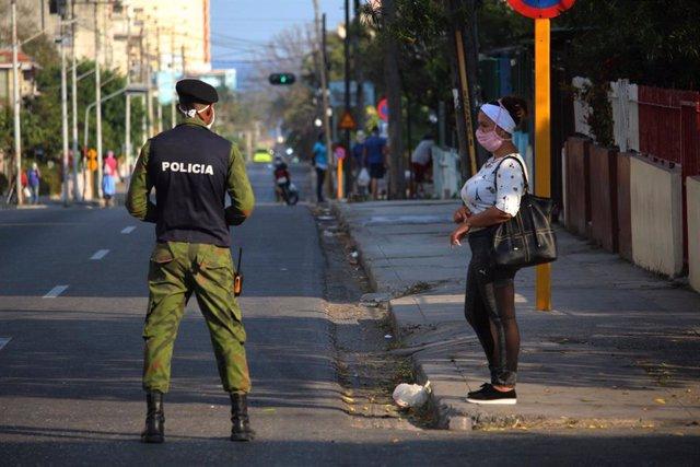 Una mujer con mascarilla junto a un policía en La Habana
