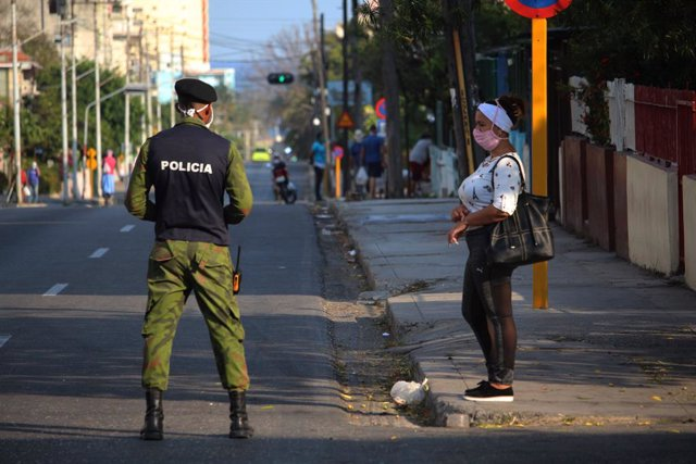 04 April 2020, Cuba, Havana: A policeman wears a face mask as he stands next to a woman in a deserted street in the El Carmelo district. Cuba has sealed off a part of downtown Havana popular with tourists because of the Coronavirus pandemic. Photo: Guille