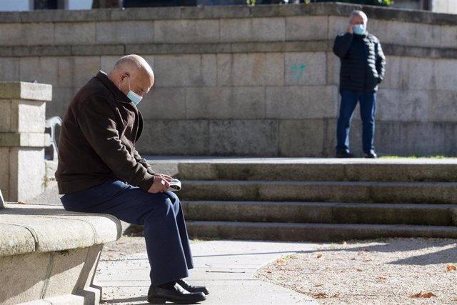 Una persona lee en un banco el mismo día de la entrada en vigor de nuevas restricciones impuestas por la crisis del Covid-19 en el municipio de Vilalba, Lugo, (España), a 21 de noviembre de 2020. Entre las medidas, además del cierre perimetral, se incluye
