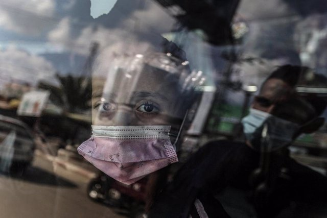 FILED - 16 November 2020, Palestinian Territories, Deir Al Balah: A Palestinian girl wearing a mask looks out of the car window. Photo: Ashraf Amra/APA Images via ZUMA Wire/dpa