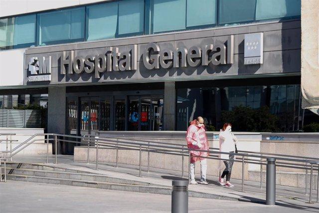 Dos personas protegidas con mascarillas salen del Hospital La Paz.