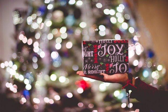 Regalo frente a un árbol de Navidad.