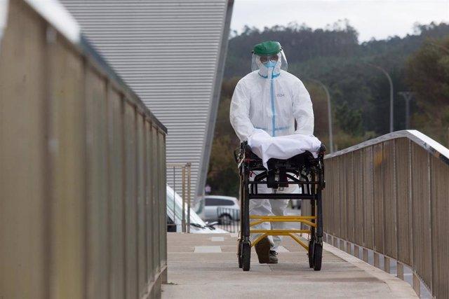 Un trabajador sanitario totalmente protegido traslada una camilla en las inmediaciones de la residencia de ancianos de San Cibrao.