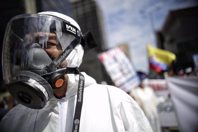 Un hombre con un traje de protección durante una protesta en Bogotá