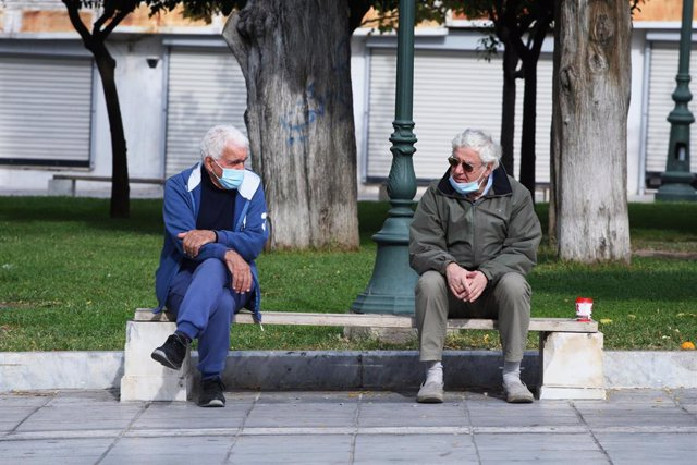 Dos hombres con mascarilla dialogan en un parque de Atenas