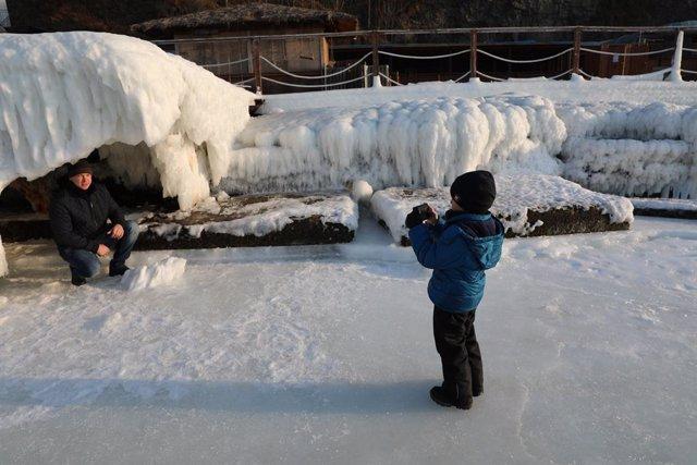 Imagen de archivo de un hijo fotografiando a su padre en un río congelado en Vladivostok, en el extremo oriental de Rusia