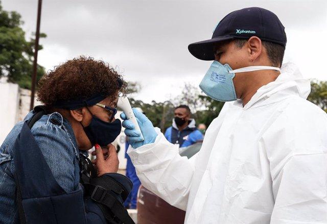 Un sanitario toma la temperatura a una mujer en Sao Paulo.