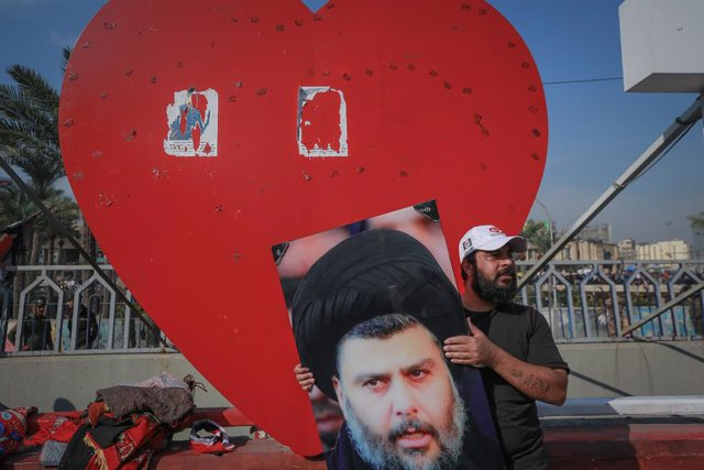 27 November 2020, Iraq, Baghdad: A supporter of Iraqi Shia cleric Muqtada al-Sadr holds his photo as he takes part in a rally in support of him at Tahrir Square. Al-Sadr called on Friday the masses of the Sadrist Movement to achieve a large majority in th
