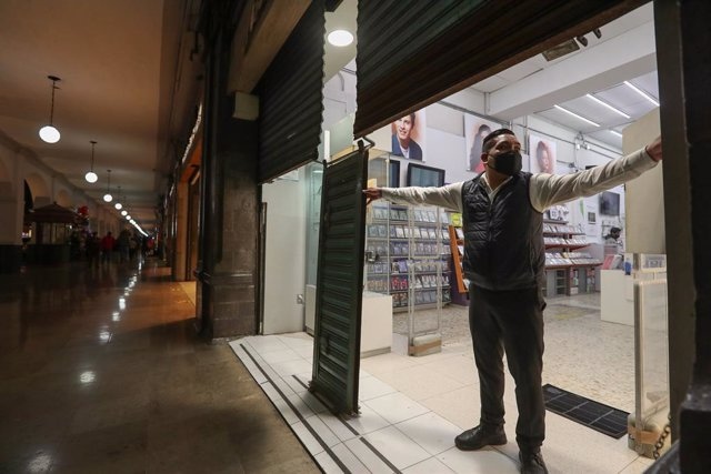 23 November 2020, Mexico, Toluca: A man closes a shop in implementation of government decisions to close shops at 7 pm to curb the spread of the coronavirus (Covid-19). Photo: -/El Universal via ZUMA Wire/dpa