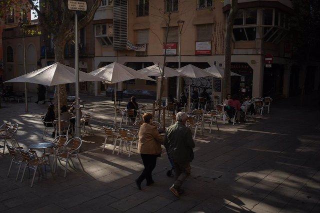 Dues dones caminen davant d'una terrassa durant el primer dia de l'inici del primer tram de la desescalada de la segona onada pel coronavirus a Barcelona.