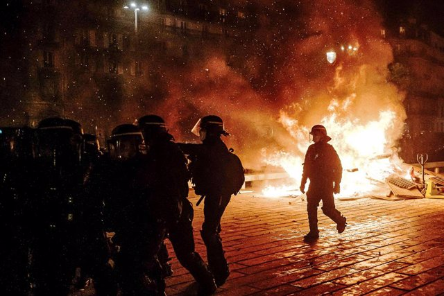 28 November 2020, France, Paris: Police officers stand next to a fire during a demonstration against brutality and the controversial Global Security bill that will restrict video recordings of police operations. Photo: Jan Schmidt-Whitley/Le Pictorium Age
