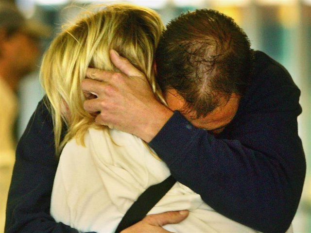 A weeping couple embace after laying a floral tribute at King's Cross Station on July 8, 2005 in London, England. More than 50 people were killed and 700 injured during a series of explosions in the morning rush hour the previous day.