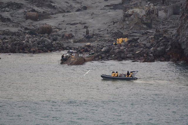 HANDOUT - 13 December 2019, New Zealand, Whakaari: Emergency personnel take part in a recovery operation to retrieve the remaining bodies on White Island following the Whakatane volcanic eruption on Monday. Photo: -/NEW ZEALAND DEFENCE FORCE via AAP/dpa -