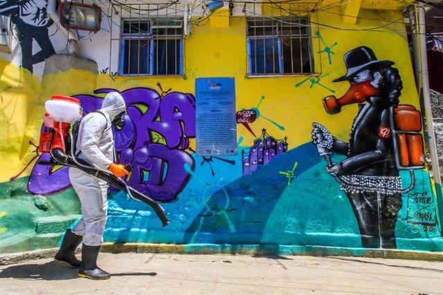 Una persona trabaja en labores de sinfección de una favela de Río de Janeiro, en el sureste de Brasil.