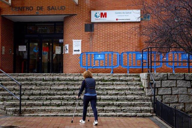 Una mujer sube con una muleta las escaleras del Centro de Salud de Colmenar Norte en Colmenar Viejo.