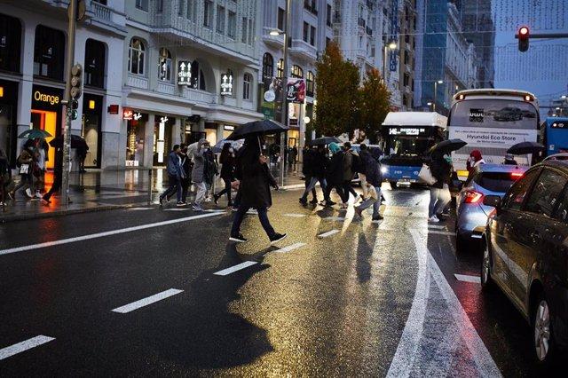 Transeúntes caminan por Gran Vía, cerca de una zona comercial de la calle de Preciados, en Madrid (España), a 27 de noviembre de 2020. La ciudad de Madrid estrena este viernes el dispositivo policial de Navidad que da comienzo con la campaña comercial del