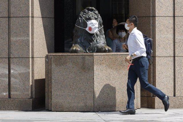 Un hombre y una estatua de un león con mascarilla en Tokio, Japón