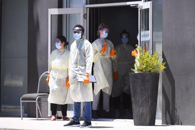 Trabajadores con equipos de protección esperan a la llegada de viajeros australianos que tendrán que pasar la cuarentena en un hotel de Canberra