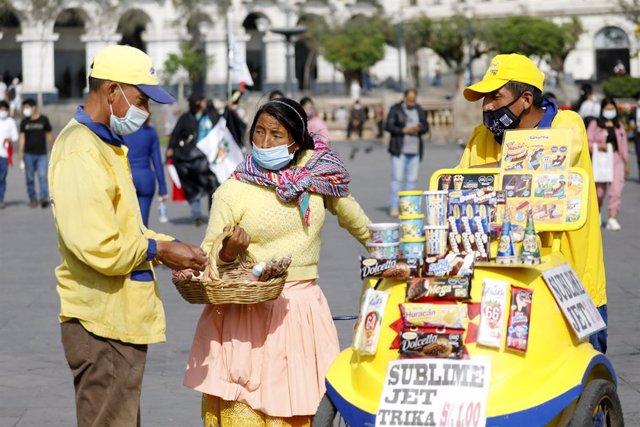 Personas con mascarilla en una plaza de Lima