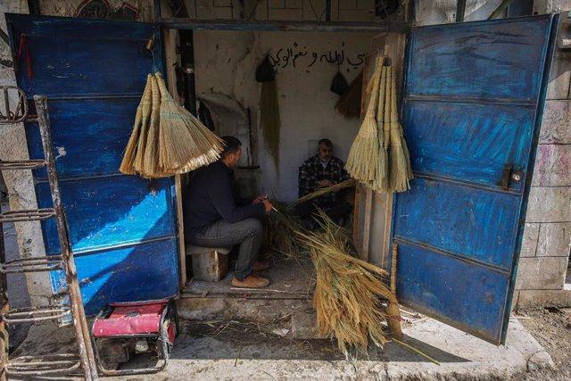 Trabajadores en un taller artesanal de escobas en la ciudad siria de Idlib