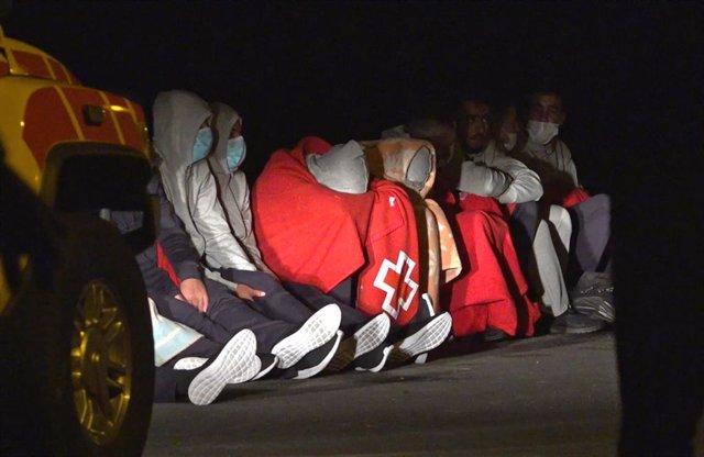 Tapadas con mantas de Cruz Roja. algunas de las 27 personas que lograron llegar a tierra con vida tras el vuelco de la patera en la que viajaban, en Lanzarote, Canarias (España), a 24 de noviembre de 2020.