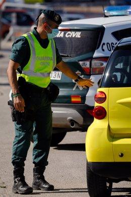Un agente de la Guardia Civil le da el alto a un pasajero durante un control de movilidad en Alguazas, Murcia (España)