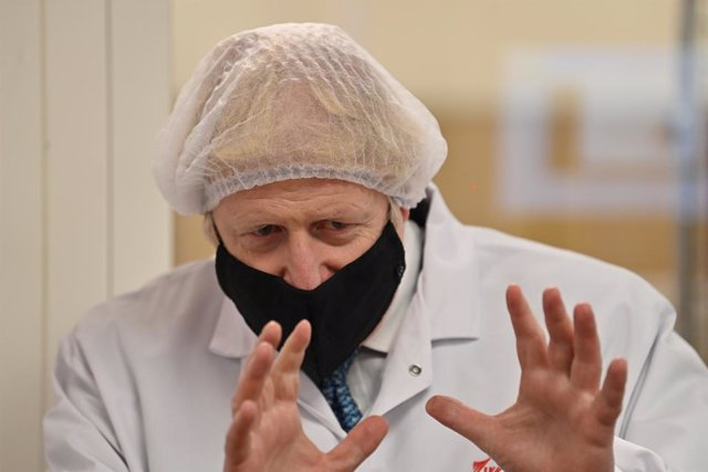30 November 2020, Wales, Wrexham: UKPrime Minister Boris Johnson watches quality testing at the 'fill and finish' stage of the manufacturing process of Covid-19 vaccines, during a visit to Wockhardt's pharmaceutical manufacturing facility following the l