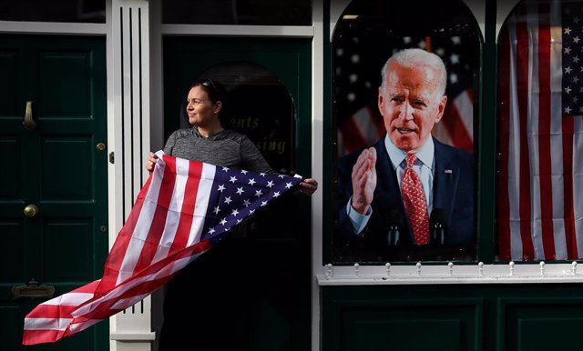 07 November 2020, Ireland, Ballina: Catherine Hallahan, owner of Hallihan's barbers, in Ballina holds the us national flag  as residents begin celebrations in the ancestral home of US Presidential candidate Joe Biden in anticipation of the results of the