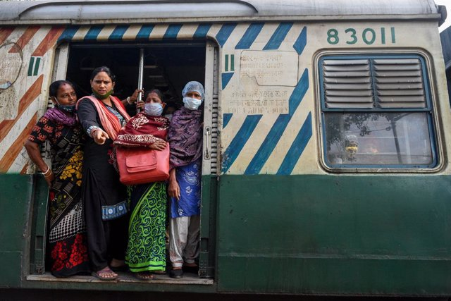 26 November 2020, India, Kolkata: Passengers stand in the train and express their opposition to the strike across India and the railway blockades during a protest calling for a nationwide strike against the current Indian governments' policies against the