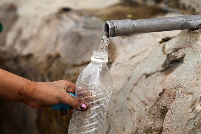 Mujer llenando una botella de agua en un grifo en la calle