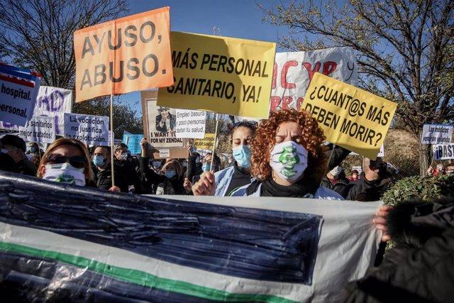 Varias personas se manifiestan con pancartas durante una concentración convocada por la plataforma Sanitarios Necesarios en la puerta del Hospital Enfermera Isabel Zendal