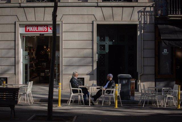 Dos homes en una terrassa durant el primer dia de l'inici del primer tram de la desescalada de la segona ona pel coronavirus a Barcelona, Catalunya (Espanya), a 23 de novembre de 2020. Des d'avui, bars i restaurants podran obrir de 6.00 a 21.30
