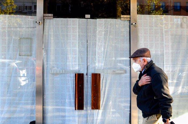 Imagen de archivo de un hombre pasando por delante de una cafetería durante la pandemia.