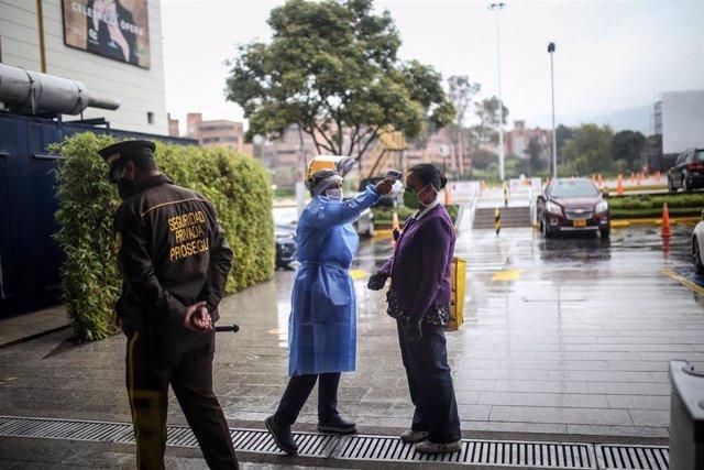 Una persona se somete a una prueba de temperatura antes de entrar a un centro comercial de Bogotá, Colombia.