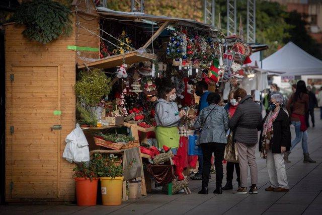 Tres señoras en uno de los 121 puestos que este año forman parte de la 'Fira de Santa Llúcia', el mercado de Navidad más antiguo de Barcelona, Catalunya (España), a 30 de noviembre de 2020. Este año la feria dispondrá de 121 puestos en lugar de las 280 de