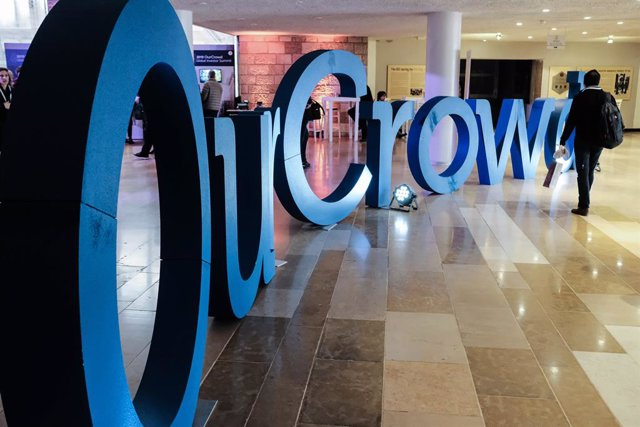 """07 March 2019, Israel, Jerusalem---: A visitor walks by the logo of """"OurCrowd"""" during the 2019 OurCrowd Global Investor Summit. Photo: Nir Alon/ZUMA Wire/dpa"""
