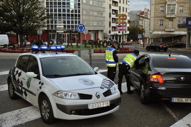 Dos agentes paran a un vehículo en un control realizado en O Carballiño, Ourense.