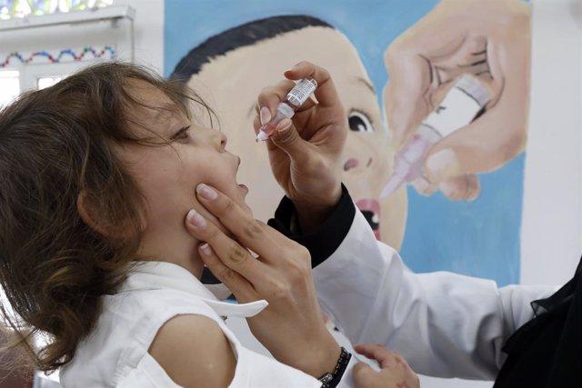 Una trabajadora sanitaria da una dosis de la vacuna contra la polio a una niña en Yemen.