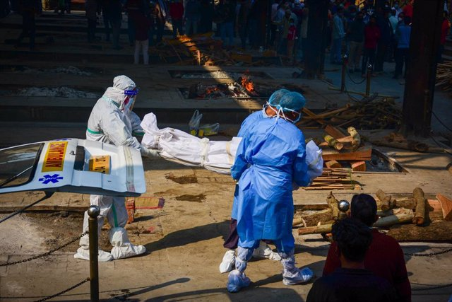 19 November 2020, India, New Delhi: Health workers carry the body of a coronavirus at the Nigambodh Ghat crematorium. Photo: Manish Rajput/SOPA Images via ZUMA Wire/dpa
