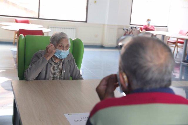 Un anciana residente recibe a un familiar durante la pandemia.