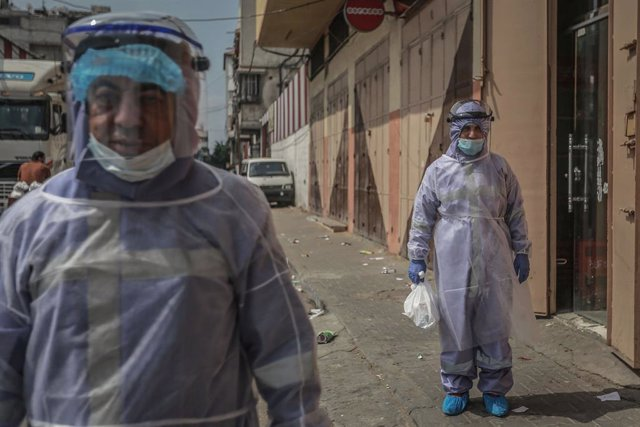 01 September 2020, Palestinian Territories, Gaza City: United Nations Relief and Works Agency for Palestine Refugees (UNRWA) employees wearing protective clothes distribute medicines to those with chronic diseases during the outbreak of the Coronavirus (C