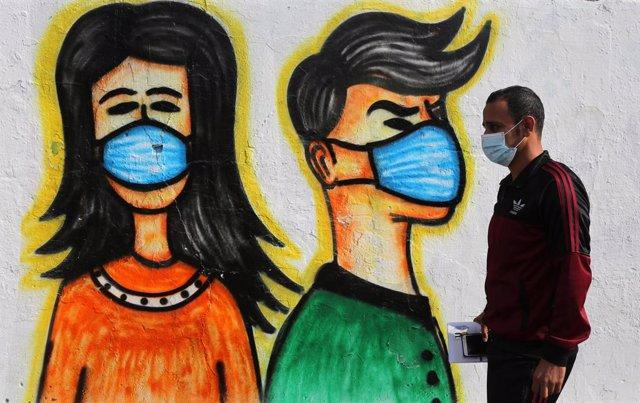 Un palestino con mascarilla pasa ante un mural en Deir al Balá, en la Franja de Gaza