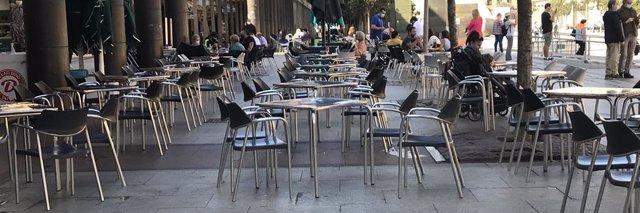 Terraza con mesas vacías en una céntrica plaza