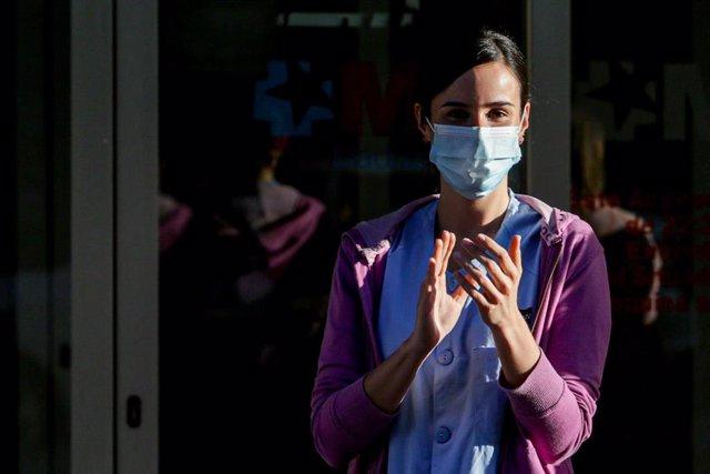 Una sanitaria del Hospital General Universitario Gregorio Marañón y un transeúnte aplauden a las puertas del hospital tras la convocatoria a través de las redes sociales de un último aplauso en homenaje a los profesionales sanitarios y demás sectores que