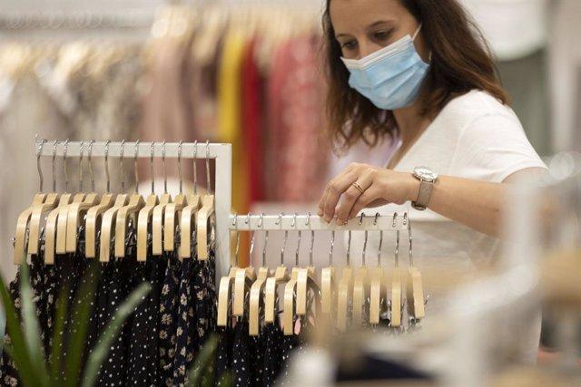 Mujer con mascarilla en una tienda de ropa.