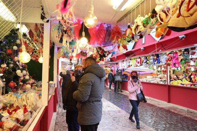 Varias personas caminan entre los puestos de un mercadillo navideño (Archivo)